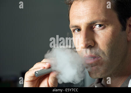 Man smoking electonic cigarette - Stock Photo