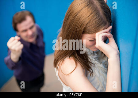 Tearful woman with her back to an aggressive man waving a clenched fist at her. - Stock Photo