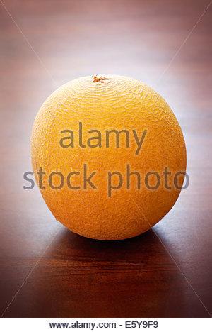 Single yellow galia melon on a wooden tabletop