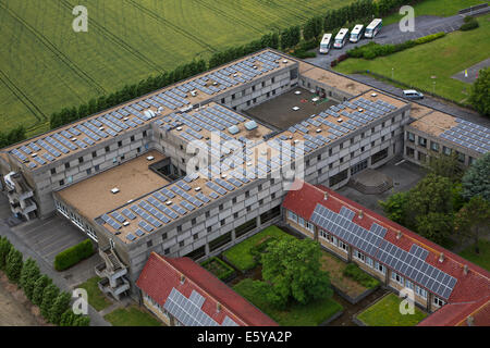 Photovoltaic solar panels on roof providing electricity by sun energy to office buildings - Stock Photo