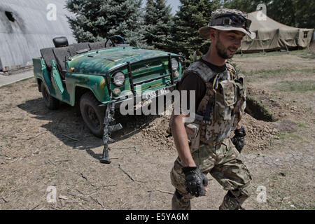 Border Troops soldier  shows an army off-road vehicle without a roof after mortar shell square hit at Novoazovsk - Stock Photo