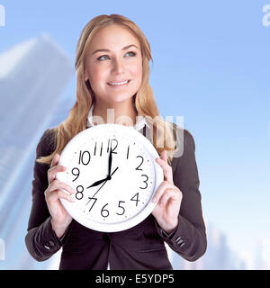 Portrait of happy smiling business woman holding in hands big clock outdoors, come to work on regular schedule, - Stock Photo