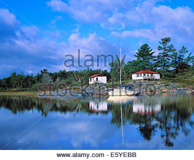 Summer cottage and sailboat on Georgian Bay, part of the Great Lakes, near Parry Sound Muskoka Ontario Canada - Stock Photo