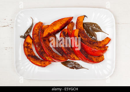 Roasted pumpkin slices served on white plate from above - Stock Photo