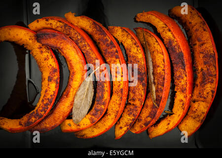 Closeup of roasted and spiced pumpkin slices on black plate from above - Stock Photo