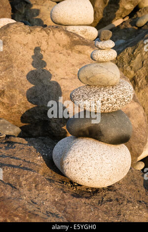 The sun sets bathing polished stacked rock on the sea shore - Stock Photo