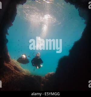 Scuba divers swimming underwater in bright blue Mediterranean Sea - Stock Photo