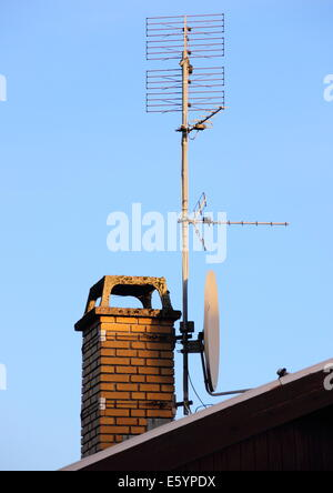 Antenna and satellite dish on a chimney - Stock Photo