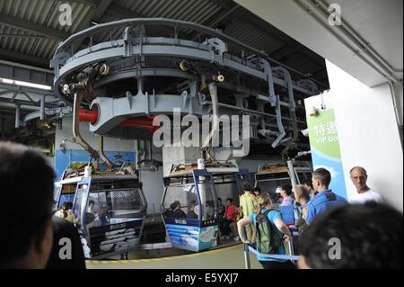 Gondolas being boarded at the top of the Ngong Ping 360 Cable Car, Lantau Island, Hong Kong - Stock Photo