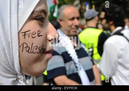 Berlin, Germany. 09th Aug, 2014. Free Palestine is painted on the cheek of a young woman outside of the Axel Springer - Stock Photo