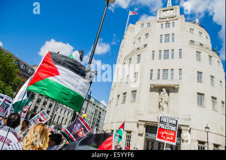 London, UK. 9th august, 2014. Outside the BBC a huge flag is unfurled and as the march heads off peace signs alternate - Stock Photo