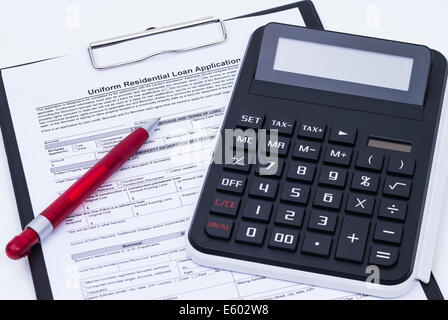 Unfilled loan application form with calculator, pen and notepad - Stock Photo