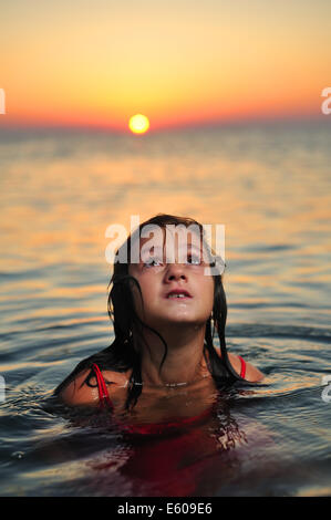 Young girl in red dress standing in sea at sunset - Stock Photo