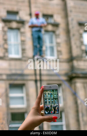 A woman's hand holding a mobile phone and recording a street performer doing a trapeze act at the Edinburgh Fringe - Stock Photo
