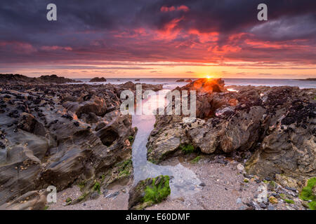 Dramatic fiery sunset on Little Fistral beach at Newquay in Cornwall - Stock Photo