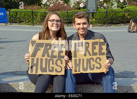 Portrait of a young man & woman holding sign saying FREE HUGS. In Union Square Park, new York City. - Stock Photo