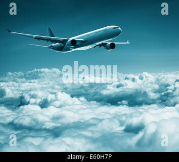 A passenger plane flies over cumulus clouds - Stock Photo