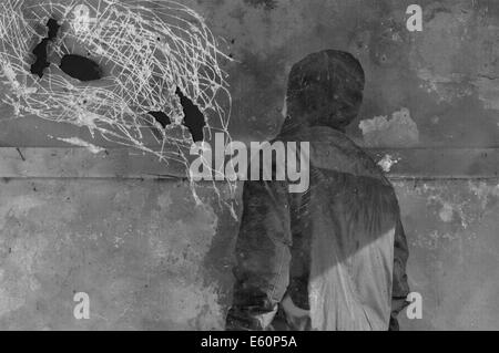 Man looking at strange shapes on textured wall surface. Black and white on scratched paper. - Stock Photo