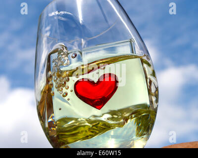 Conceptual image of white wine swirling in glass with heart motif with blue sky behind - Stock Photo