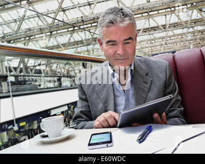 Mature businessman seated at cafe table on railway concourse looking at his iPad tablet computer with iPhone and - Stock Photo