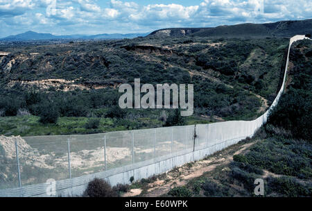 A continuous wire fence marks the border in the rugged countryside between the U.S. and Mexico near Tijuana in the - Stock Photo