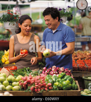 A Latino couple shop for fresh produce at a farmers market November 5, 2012 in Baltimore, Maryland. - Stock Photo