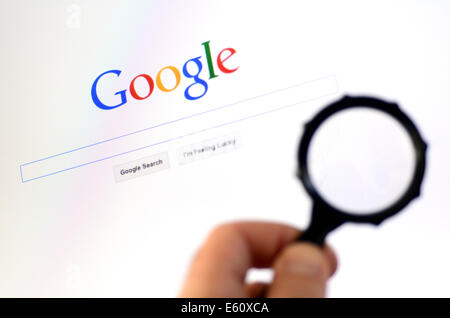 AUCKLAND - AUG 10 2014:Man hand holds Magnifying glass against Google homepage.According to the Washington Post - Stock Photo