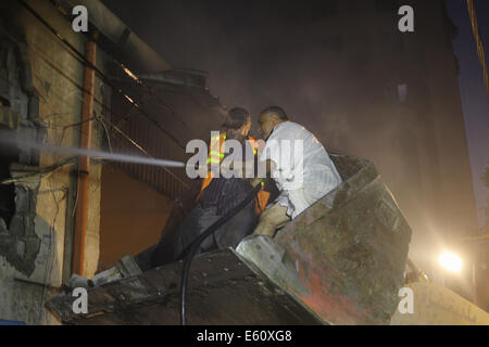 Gaza. 10th August, 2014. Palestinian firefighters trying to extinguish a fire in a chemical factory, west of Gaza - Stock Photo