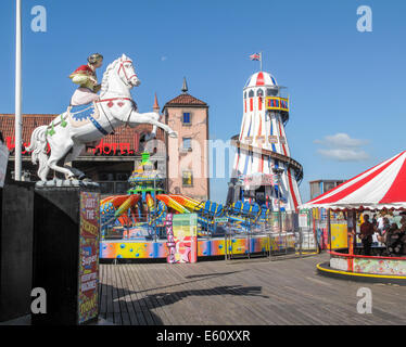 South coast sightseeing: Helter skelter and colourful fairground attractions at the funfair on Brighton Pier popular for family holidays in summer