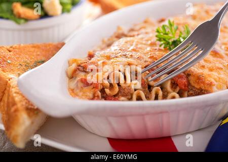 A freshly baked homemade lasagna with garlic bread and caesar salad. - Stock Photo