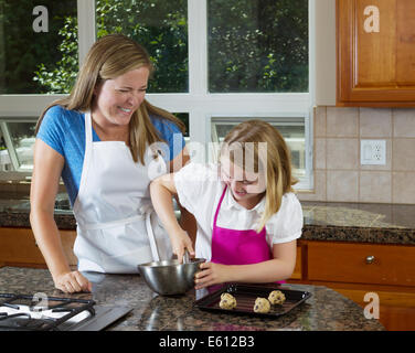 Front view of mother watching her younger daughter mixing up the raw cookie dough - Stock Photo