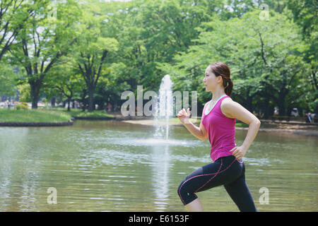 Young Japanese girl running in the park - Stock Photo
