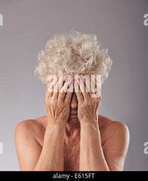 Portrait of  a upset old woman with her head in her hands against grey background. Sad senior woman covering her - Stock Photo