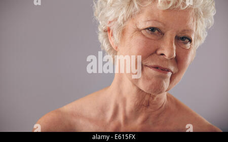 Close-up portrait of old caucasian female face against grey background. Senior woman with wrinkled skin looking - Stock Photo