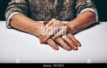 Close-up studio shot of a senior woman's hands resting on grey surface. Old lady sitting with her hands clasped - Stock Photo