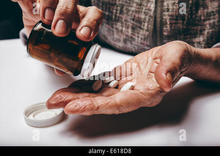 Close-up image of senior woman taking out pills from the pills bottle. Focus on hands. Old female taking medicines. - Stock Photo