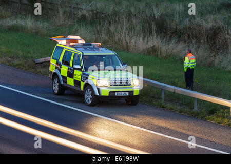 A Highways Agency landrover vehicle attends the scene of a traffic incident on a UK motorway at dusk. - Stock Photo