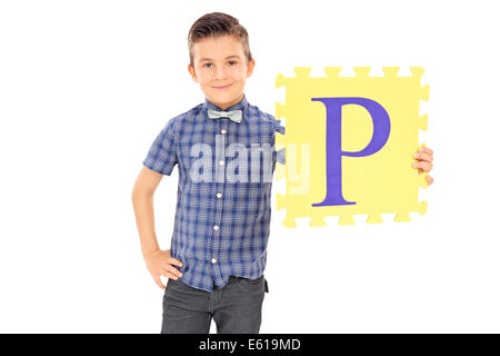 Little boy holding yellow piece of a puzzle - Stock Photo