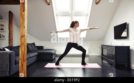 Full length image of attractive young woman exercising on mat in living room. Fit lady doing yoga at home. - Stock Photo
