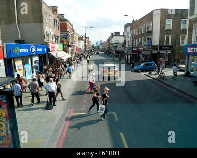 View of Kingsland Road high street & police car looking towards Central City of London & young women crossing street - Stock Photo