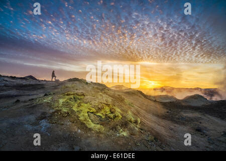 Woman standing by geothermal hot springs, mud pots and fumaroles, Namaskard close to Lake Myvatn, Northern, Iceland - Stock Photo