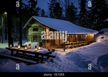 Santa's cottage in the Finnish deep forest, lit with oil lamps, full of feeling. Deep snow and a sleepy, dreamy - Stock Photo