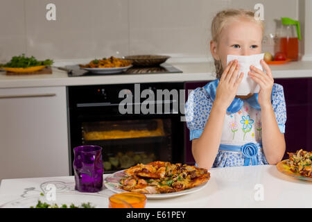 Little blond girl eating a large plate of pizza sitting at the kitchen table wiping her mouth on a napkin - Stock Photo