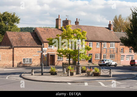 Roundabout in Church Street in the village centre of Great Bedwyn, Wiltshire, UK, and traditional row of red brick - Stock Photo