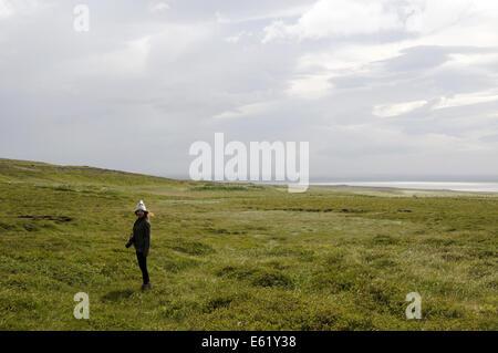 Girl on windy coastline along Snaefellsnes Peninsula in Northern Iceland - Stock Photo