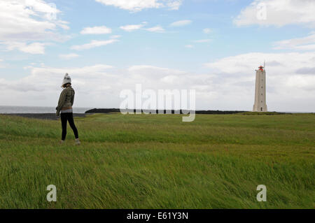 Tourist visiting the Malarrif Lighthouse on Snaefellsnes Peninsula in Northern Iceland - Stock Photo