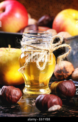 Glass jar of honey with apples, chestnuts and walnuts over black wooden table - Stock Photo
