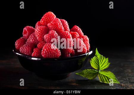 Bowl of fresh raspberry on dark background - Stock Photo