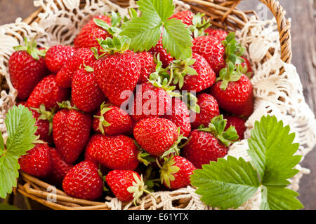 Strawberries in basket on rustic wooden background - Stock Photo