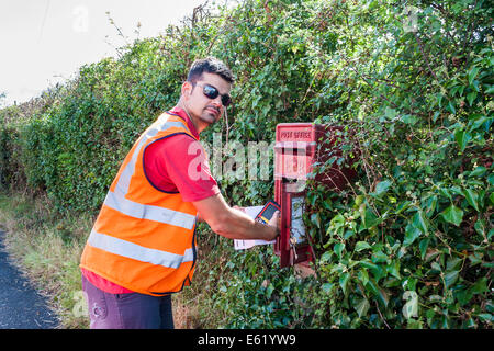 Royal Mail postman collects mail from rural pillar box - Stock Photo